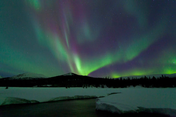 Purple northern lights over a lake